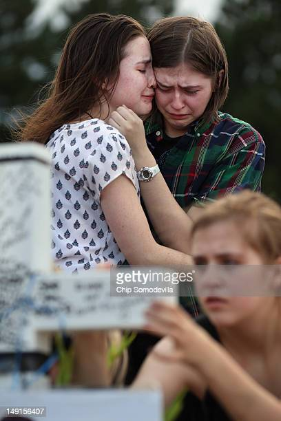 Two daughters of movietheatershootingvictim Gordon Cowden's embrace one another as another daughter leave messages on a cross at the makeshift...