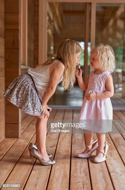 Zwei Töchter, die einander mit Mutter Lippenstift bemalt