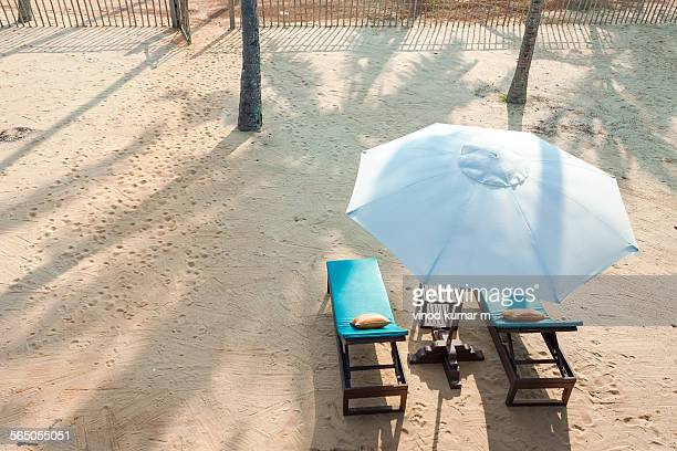 Two deck chairs and an umbrella  on beach side