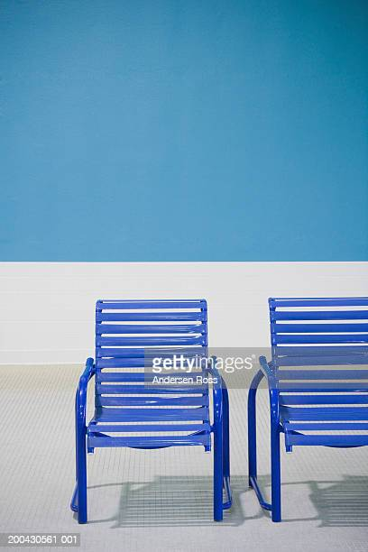 Two deck chairs on tiled floor