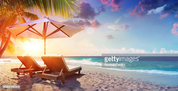 Two Deckchairs Under Parasol In Tropical Beach At Sunset : Stock Photo