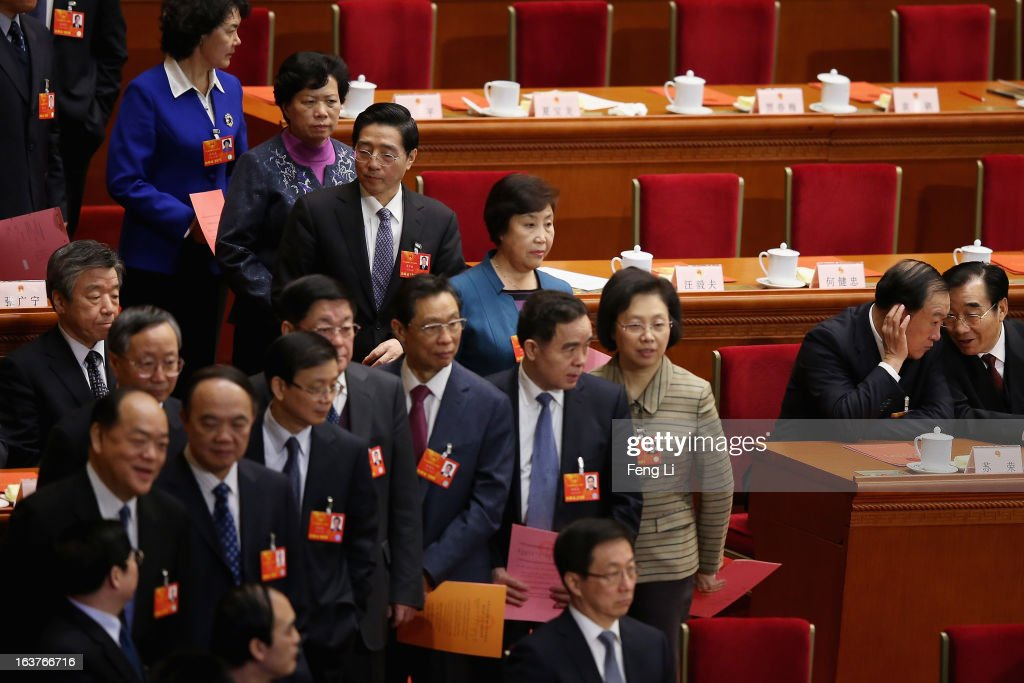 Two delegates whisper as other delegates waiting to cast their votes into a box during the fifth plenary meeting of the National People's Congress at the Great Hall of the People on March 15, 2013 in Beijing, China. Li Keqiang was elected as China's Premier Friday at the 12th National People's Congress, the country's top legislature.