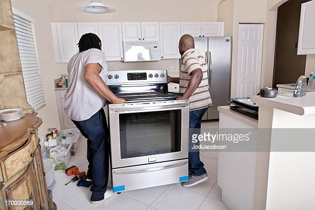 two delivery men installing an oven