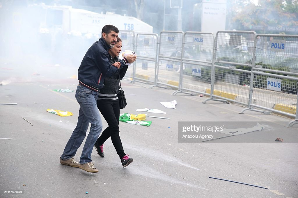 Two demonstrator from a group, rejecting police's security check and carrying illegal materials, flee from riot police's intervention as they try to enter the open market area in the Bakirkoy neighborhood, where main May Day celebrations take part on May 01, 2016 in Istanbul, Turkey. Every year May Day is observed and commemorated as an official holiday all around Turkey.