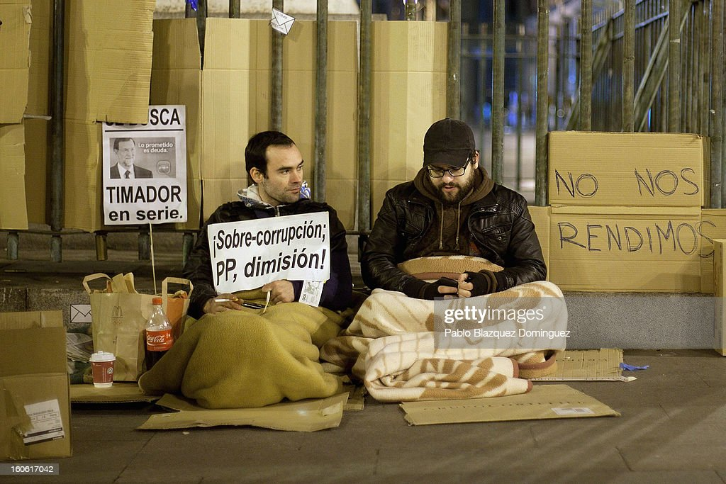 Two demonstrators camp at a protest in Puerta del Sol Square after a demonstration against alleged corruption scandals implicating the PP (Popular Party) on February 3, 2013 in Madrid, Spain. Spain's Prime Minister Mariano Rajoy yesterday denied receiving undeclared payments from his political party. More information on secret payments were revealed today and leader of opposition socialist Party (PSOE) urged Rajoy to resign.