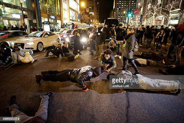 Two demonstrators do pushups as others block motorist along Michigan Avenue as they protest the shooting of Laquan McDonald who was killed by a...