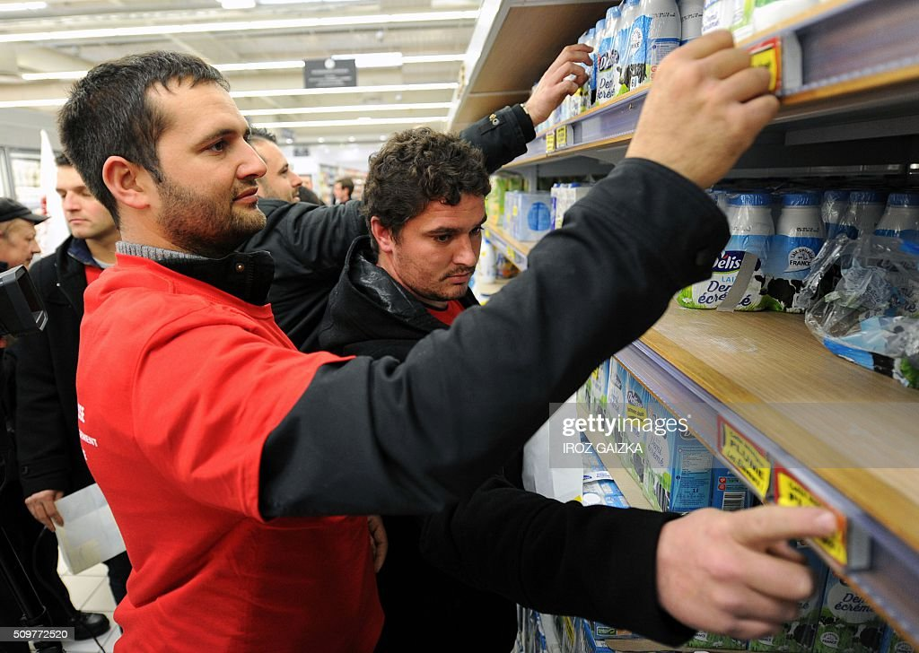 Two demonstrators stick stickers reading 'This shop rips of the farmers' on the milk shelves at a Lecler supermarket in Saint-Paul-les-Dax on February 12, 2016 during a demonstration called by the trade-union 'Young Farmers' ('Jeunes Agriculteurs') to denounce the profits done by supermarkets. Nearly 15 young farmers gathered and controled prices and origins of the products sold in a Lecler supermarket in Saint-Paul les Dax on February 12, 2016. / AFP / IROZ GAIZKA