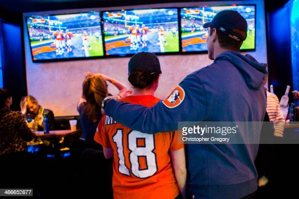 Two Denver Bronco's fans console each other in the third quarter as the Seattle Seahawks lead by 30 points in the Super Bowl at The Royal bar on...