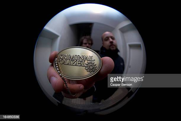 Two detectives showing a crime police (German: Kriminal Polizei) badge to a peephole