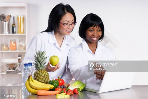 Two dietitians holding food and working online