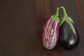 Two different eggplant types on dark fabric background: common black variety and scratched variety. Copy space on the left side.