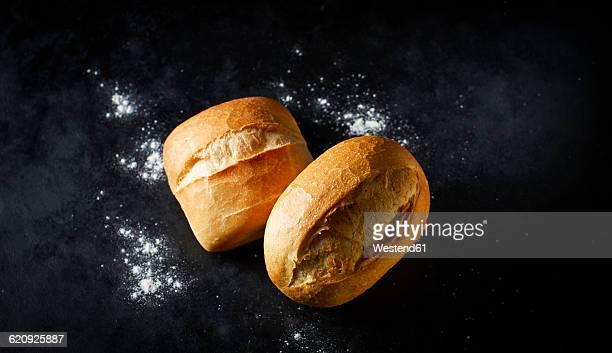 Two different wheat rolls on dark ground