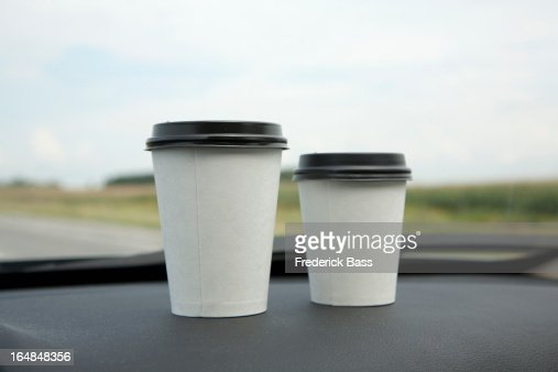 Two disposable cups of coffee on a car dashboard