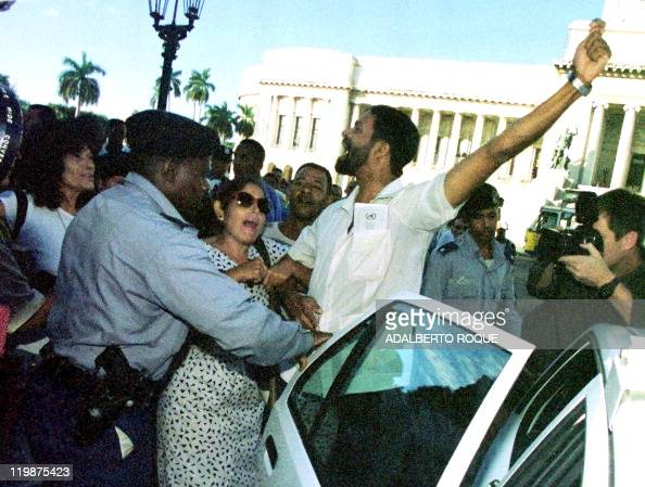 Two dissidents are pushed into a car by Cuban police after a confrontation with Castro sympathizers 27 November in Havana People opposed to the...
