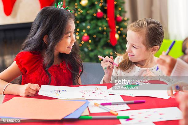 Two diverse young girls creating Christmas greeting cards