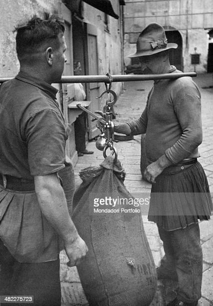 Two dock workers wearing the typical jeans scosalin weighing a sack on a pier at the Port Genoa 1950s