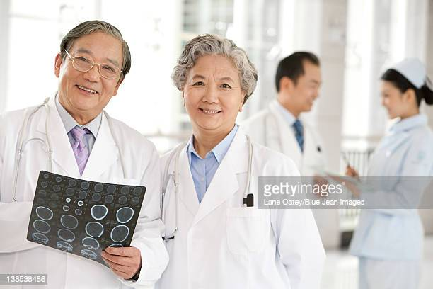 Two Doctors Examine a CAT Scan with a Doctor and Nurse in the Background