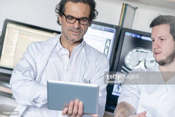 Two doctors holding tablet discussing