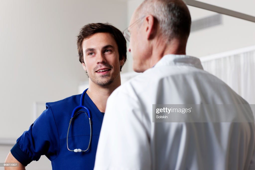 Two doctors in conversation in hospital : Stock Photo