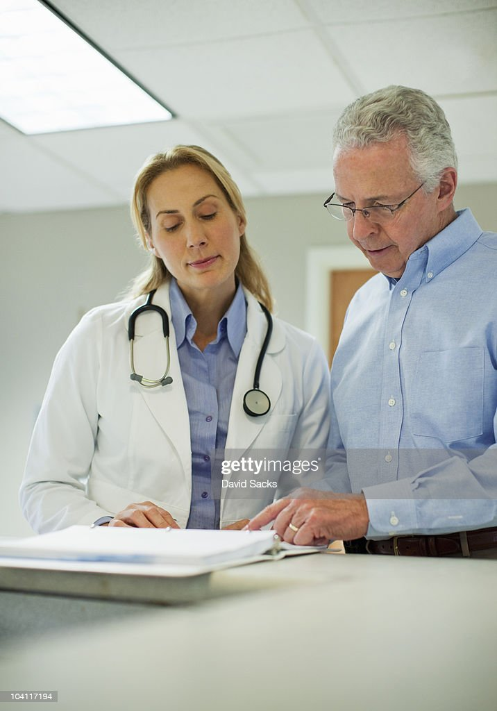 Two doctors looking at medical chart : Stock Photo