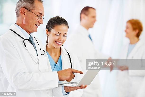 Two doctors looking at the laptop.