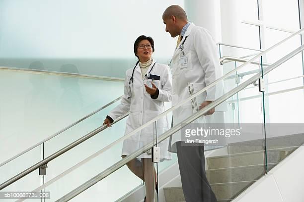 Two doctors walking on steps, talking