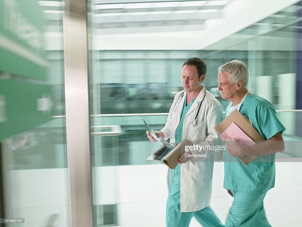 Two doctors wearing scrubs walking in hurry in hospital : Stock Photo