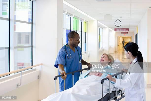 Two Doctors Wheeling Patient Down Hallway