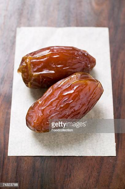 Two dried dates on paper