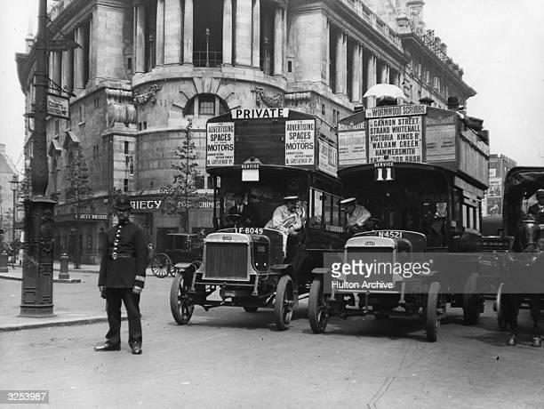 Two drivers chat from their buses outside the Gaiety Theatre London