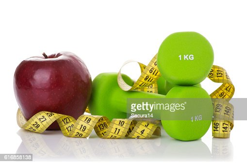 Two dumbbells, red apple, measuring tape. : Stock Photo