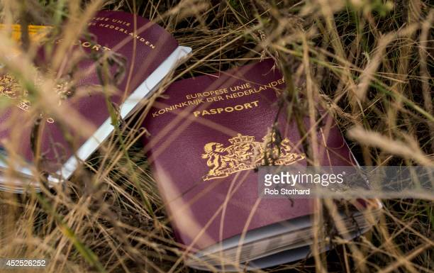 Two Dutch passports lie in a field amongst luggage personal belongings and wreckage from Malaysia Airlines flight MH17 on July 22 2014 in Grabovo...