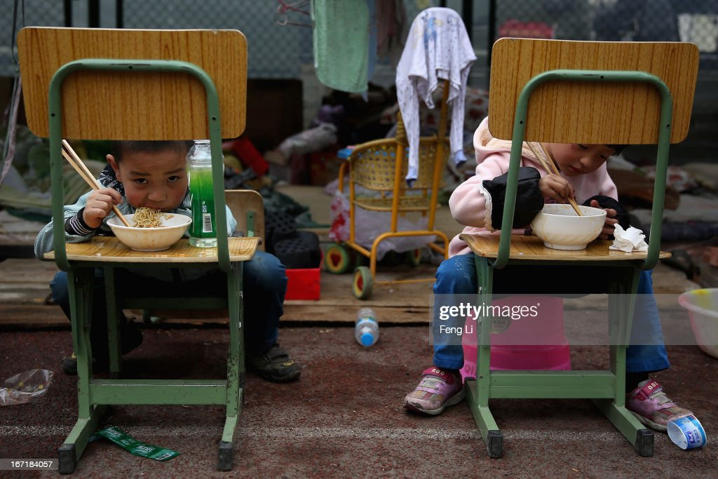 Two earthquake survivors eat instant noodles outside the tent in a middle school on April 22, 2013 in Baoxing county of Ya An, China. A magnitude 7 earthquake hit China's Sichuan province on April 20 claiming over 190 lives and injuring thousands.