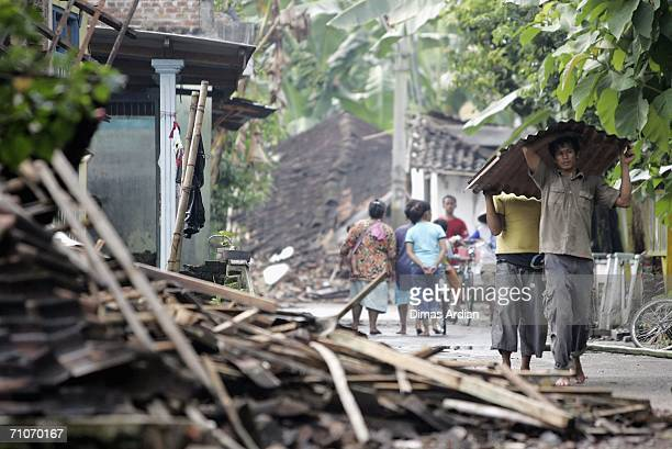 Two earthquake survivors salvage materials amid the rubble of their wrecked home in devastated Bantul regency May 28 2006 in Yogyakarta Central Java...