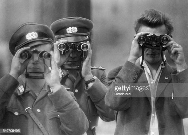 Two East German policemen and one civilian are watching with binoculars a photographer on West Berlin area during the construction of the Berlin Wall