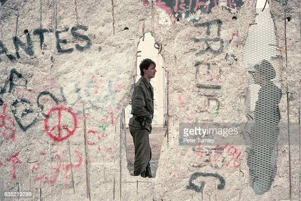 Two East German soldiers as seen through holes in the Berlin Wall