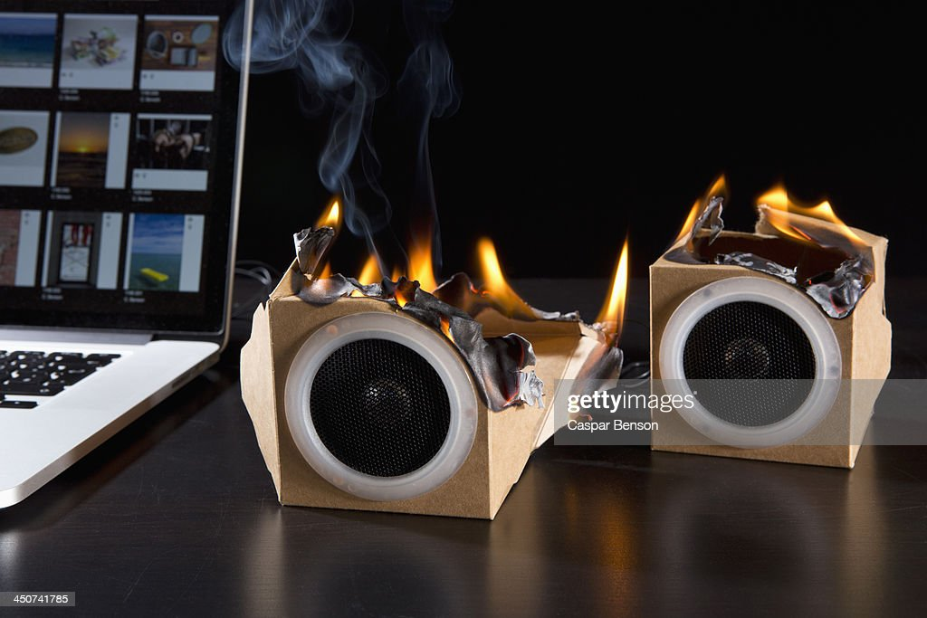 Two eco friendly cardboard audio speakers on fire next to a laptop