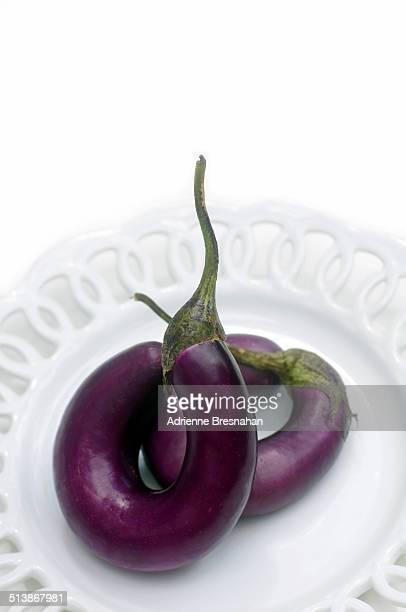 Two eggplants on a white ceramic plate