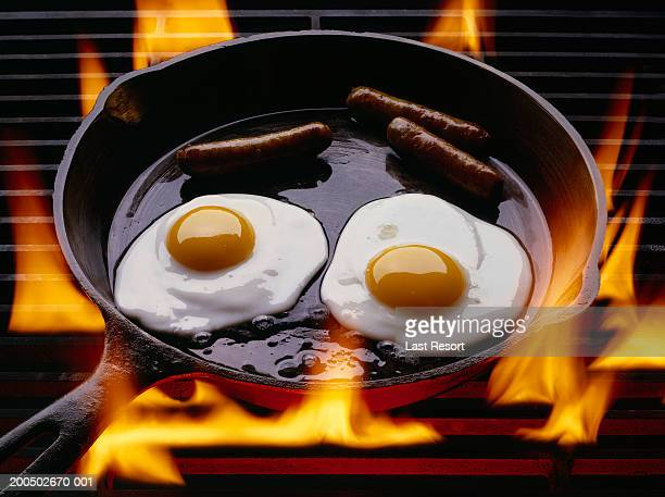 Two eggs and three sausages frying in cast iron pan on grill, close-up