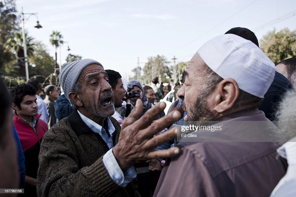 Two Egyptian men argue near Egypt's Presidential Palace, after violent clashes the previous night, on December 6, 2012 in Cairo, Egypt. At least five people were reported killed in the Cairo suburb of Heliopolis late on December 5 after thousands of protesters from groups both supporting and against President Morsi converged on the Presidential Palace, following large anti-government demonstrations in front of the palace on December 4. Anti-Morsi protesters continue to demonstrate across Egypt against the country's draft constitution, rushed through parliament in an overnight session on November 29. The country's new draft constitution, passed by a constitutional assembly dominated by Islamists, will go to a referendum on December 15.