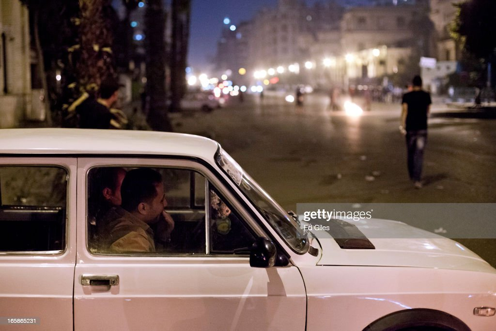 Two Egyptian men sit in a car to protect themselves from tear gas fired by nearby riot police during a demonstration against Egyptian President Mohamed Morsi and the government of the Muslim Brotherhood by the Cairo High Court on April 6, 2013 in Cairo, Egypt. Hundreds of protesters gathered at multiple locations across Cairo and other cities in Egypt to mark the fifth anniversary of the April 6 movement, a major revolutionary group made up of youth and workers in Egypt.