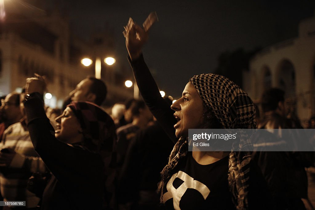 Two Egyptian protesters chant during a protest against Egyptian President Mohammed Morsi at the Presidential Palace on December 4 in in Cairo, Egypt. Thousands of protesters converged on the Presidential Palace in the Cairo suburb of Heliopolis on Tuesday evening to demonstrate against the country's draft constitution that was rushed through parliament in an overnight session on November 29. Protesters and police briefly clashed outside the Presidential Palace before riot police retreated inside the palace grounds. The country's new draft constitution, passed by a constitutional assembly dominated by Islamists, will go to a referendum on December 15.