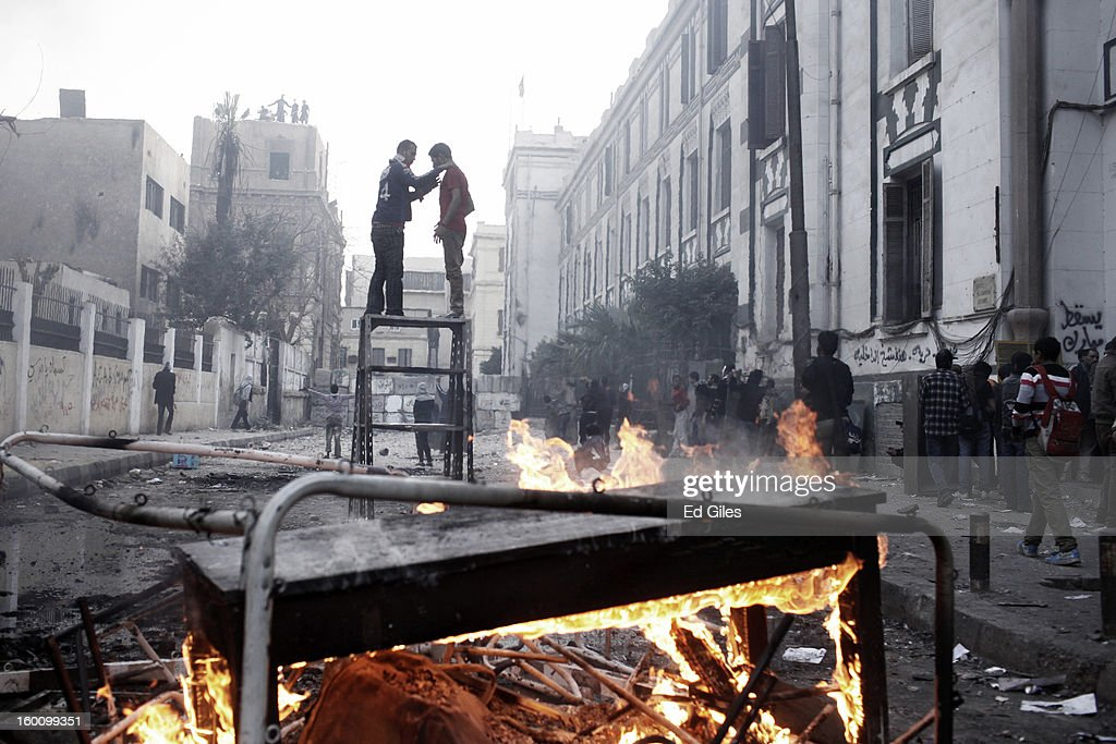 Two Egyptian protesters stand on top of a piece of furniture while riot police watch from a nearby rooftop, during a protest following the announcement of the death penalty for 21 suspects in connection with a football stadium massacre last year, on January 26, in Cairo, Egypt. Protests have continued across Egypt after a verdict was announced in a case over the deaths of more than seventy fans of Egypt's Al-Ahly football club in a stadium massacre on February 1, 2012, in the northern city of Port Said, during a brawl that began minutes after the final whistle of a match between Al-Ahly and opposing side, Al-Masry. 21 fans of the opposing side, Al-Masry, were given the death penalty in the court case, a verdict that must now be approved by Egypt's Grand Mufti. The verdict was handed down during a period of high tension across Egypt, one day after the second anniversary of the beginning of Egypt's 2011 revolution that overthrew former President, Hosni Mubarak.