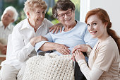 Two elder women and friendly nurse are smiling during meeting in common room