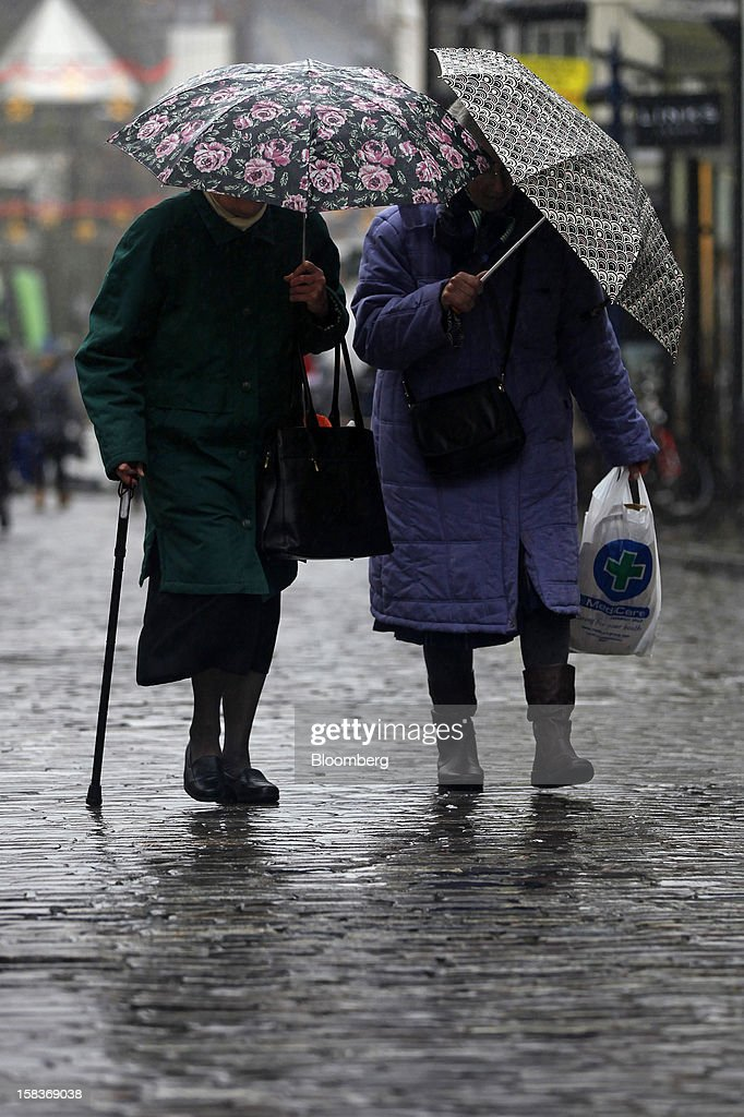 Two elderly ladies shelter from the rain as they walk up the high street in Guildford, U.K., on Friday, Dec. 14, 2012. Standard & Poor's lowered its outlook on Britain's top credit rating to negative, citing weak economic growth and a worsening debt profile. Photographer: Simon Dawson/Bloomberg via Getty Images