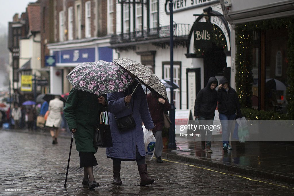 Two elderly ladies shelter from the rain beneath umbrellas as they walk along the high street in Guildford, U.K., on Friday, Dec. 14, 2012. Standard & Poor's lowered its outlook on Britain's top credit rating to negative, citing weak economic growth and a worsening debt profile. Photographer: Simon Dawson/Bloomberg via Getty Images