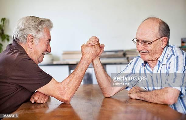 Two elderly men arm wrestling