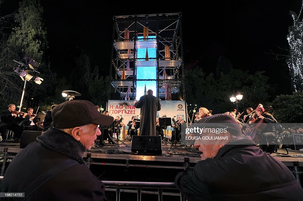 Two elderly men comment on the Christmas decorated staged during the inauguration of the Christmas season and the illumination of the central Athens Syntagma square on December 11, 2012. Organiser opted for a decorated platform rather than a Christmas tree.
