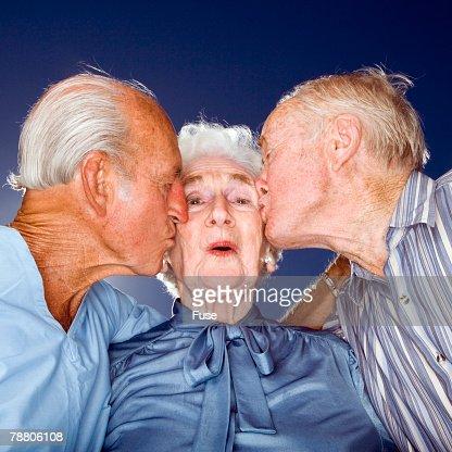 Two Elderly Men Kissing Elderly Woman