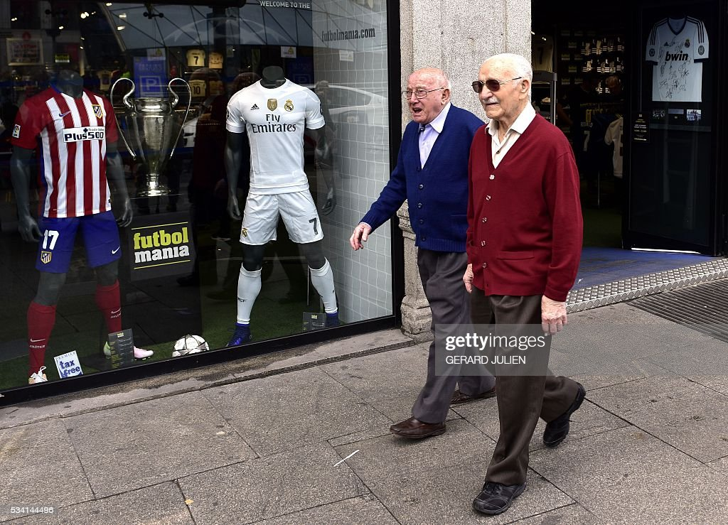 Two elderly pass by two jerseys of the Real Madrid and Atletico de Madrid football clubs displayed in a shopwindow at the Puerta del Sol square in Madrid on May 25, 2015. The two football teams of Madrid will play the UEFA Champions League final in Milan on May 28, 2016. / AFP / GERARD